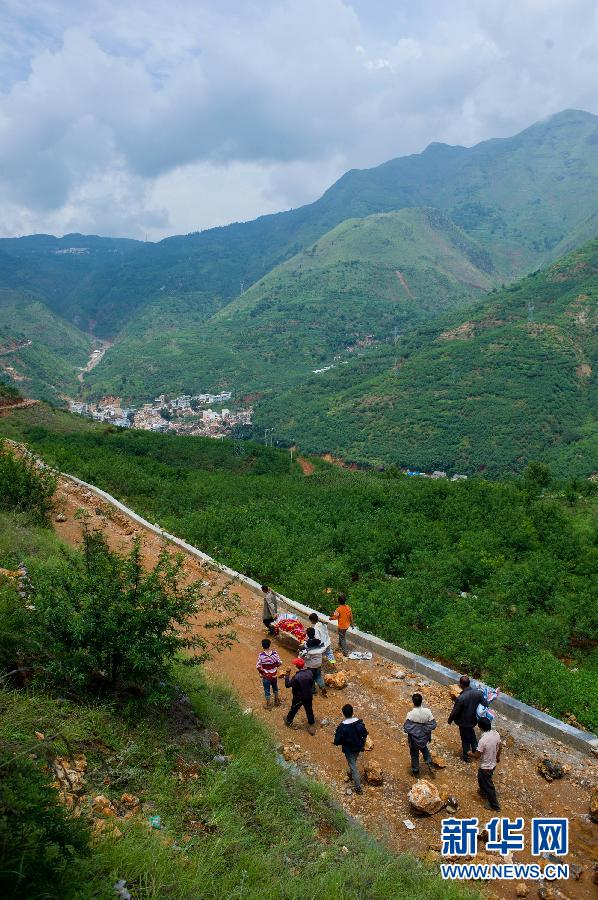 云南省鲁甸县龙头山镇龙泉村唐家湾的村民在搬运遇难者遗体,远处为图片