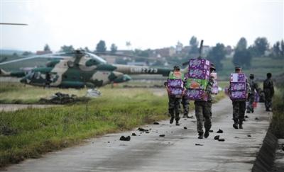 云南昭通机场,官兵在往直升机上运送救灾物资