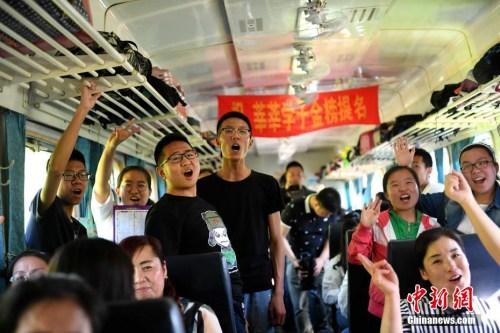 """资料图:2017年6月5日,乘坐""""高考专列""""的学生在车厢内集体加油助威。<a target='_blank'  data-cke-saved-href='http://www.chinanews.com/' href='http://www.chinanews.com/'></table>中新社</a>记者 王舒 摄"""