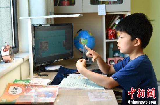 """河北小学生家中线上""""开学"""" 2月10日,河北石家庄,小学生们正在家中通过电脑、平板电脑等收看直播上课."""